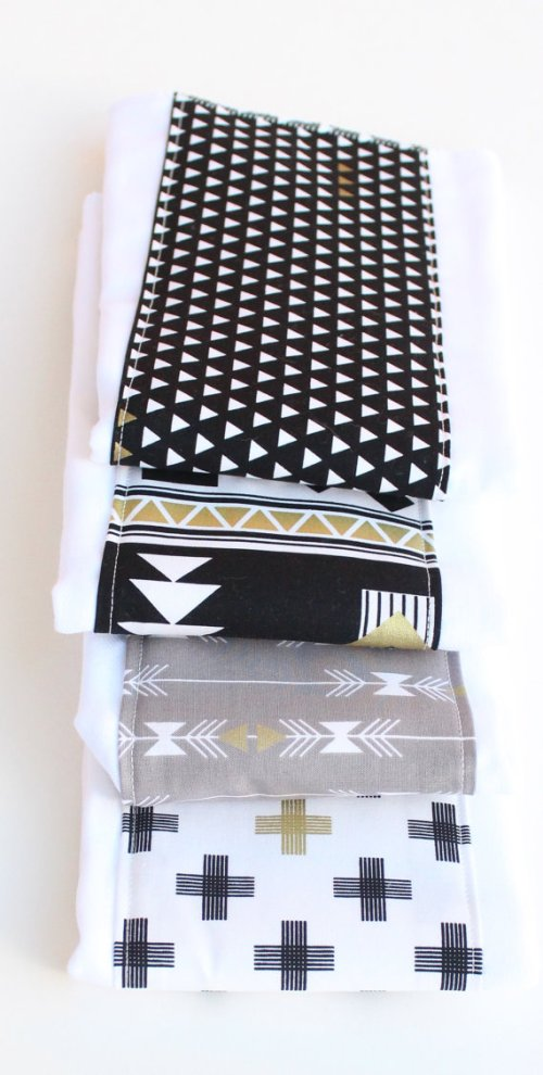 Soften it up with a bit of grey and metallics in the accessories, like these burp cloths from Etsy